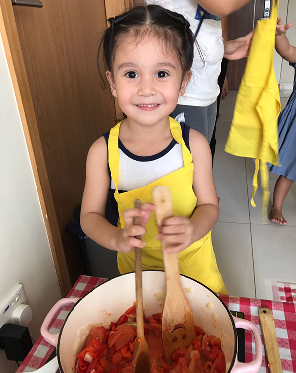 young girl smiling and cooking